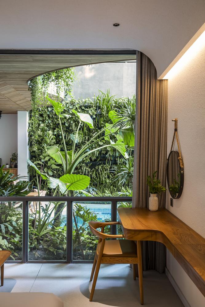Visão de um das varandas do prédio, com vista para uma vegetação volumosa e também vista para a piscina