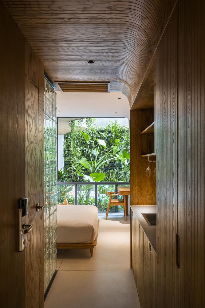Quarto com mobiliéario de madeira e rattan, materiais ecológicos, com uma cama branca e vista para a varanda com uma vegetação exuberante