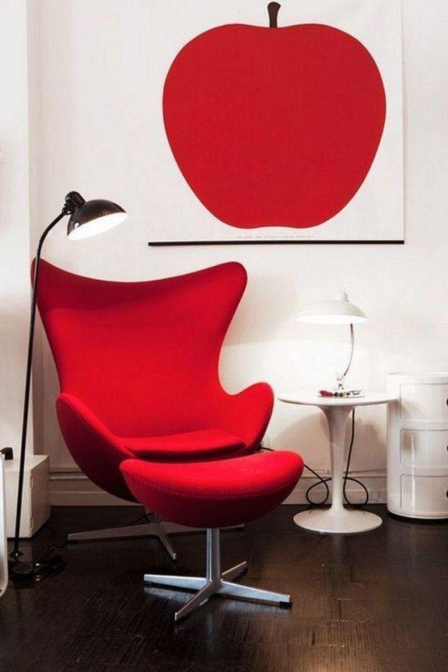 Cadeira Egg vermelha vibrante. Mesa lateral com abajur, ambos brancos. Piso em madeira, luminária metálica de chão à esquerda. Na parede branca, quadro com maçã no mesmo tom de vermelho da cadeira.