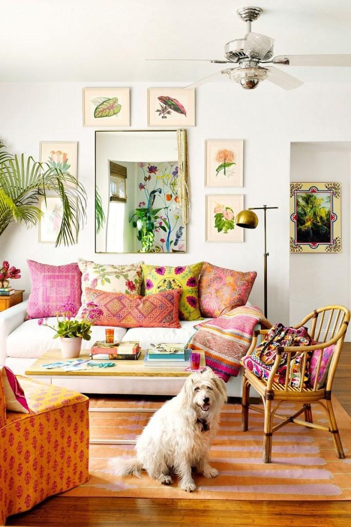 Sala em estilo boho. Sofá branco com almofadas coloridas estampadas com flores. Espelho na parede com quadros botânicos em volta. Mesa de centro em madeira. Cadeira ratan. Tapete laranja. Cachorrinho branco sentado no chão.
