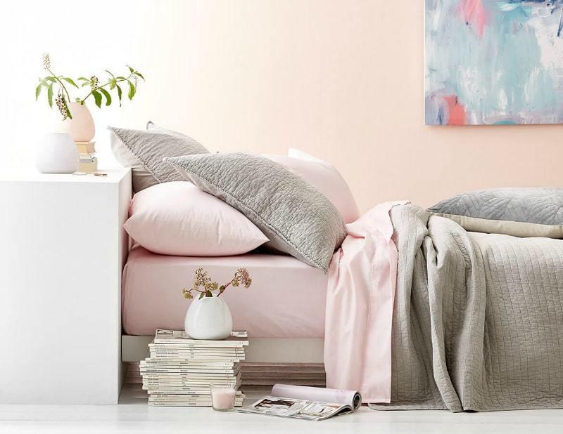 Quarto com cama baixa com lençol rosa claro e travesseiros cinzas. Cabeceira branca com vaso apoiado. Pilha de revistas com vaso pequeno em cima