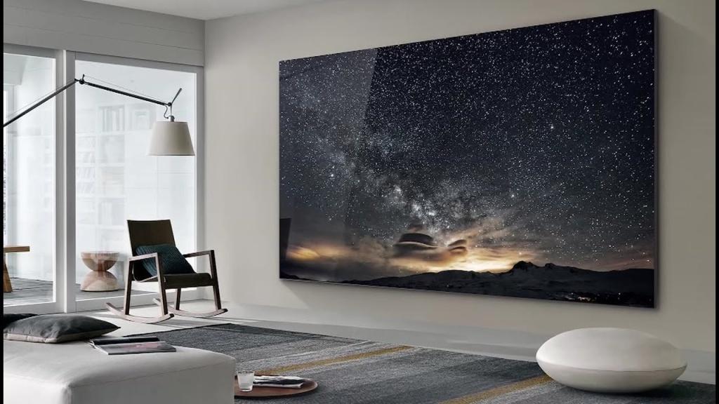 Sala de TV com grande tv cobrindo toda a parede. Na tela, imagem de céu estrelado