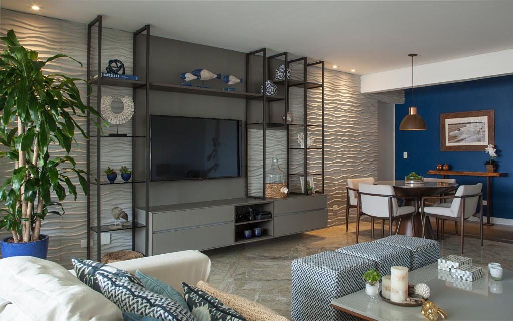 a madeira presente no painel da TV e no móvel baixo que esconde os eletrônicos se uniu às estruturas de alumínio para a composição harmônica e atemporal da sala de TV