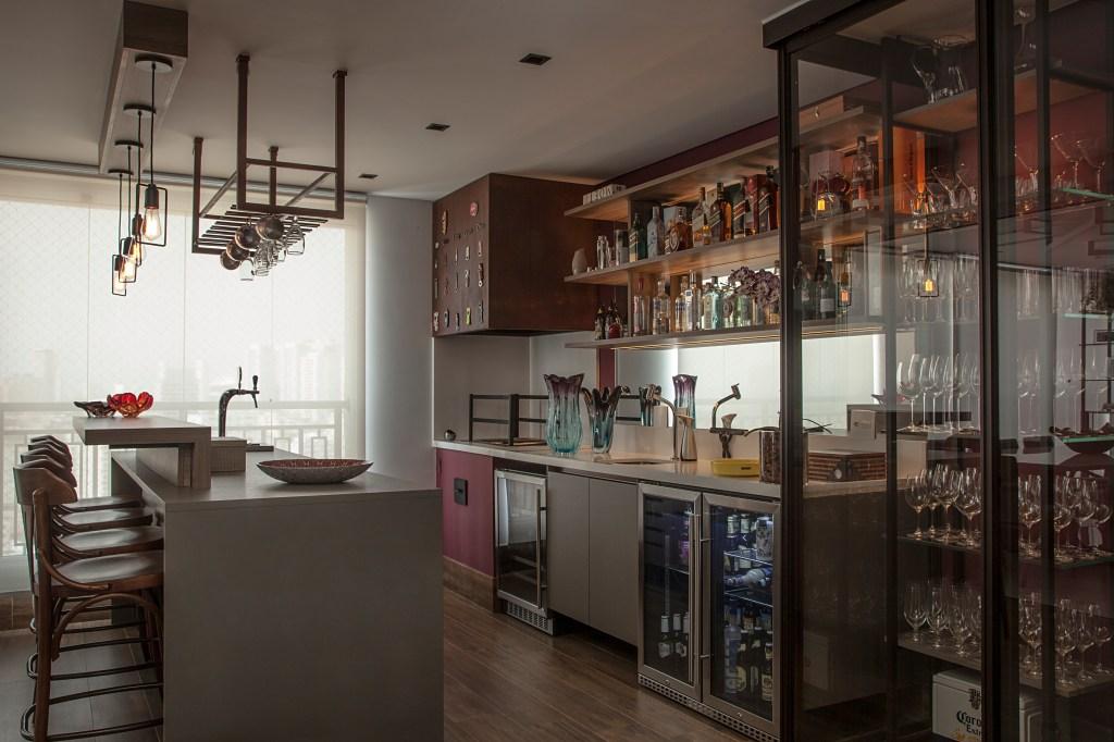 serralheria presente nos nichos fixados no forro e na cristaleira complementa o mobiliário planejado da área gourmet