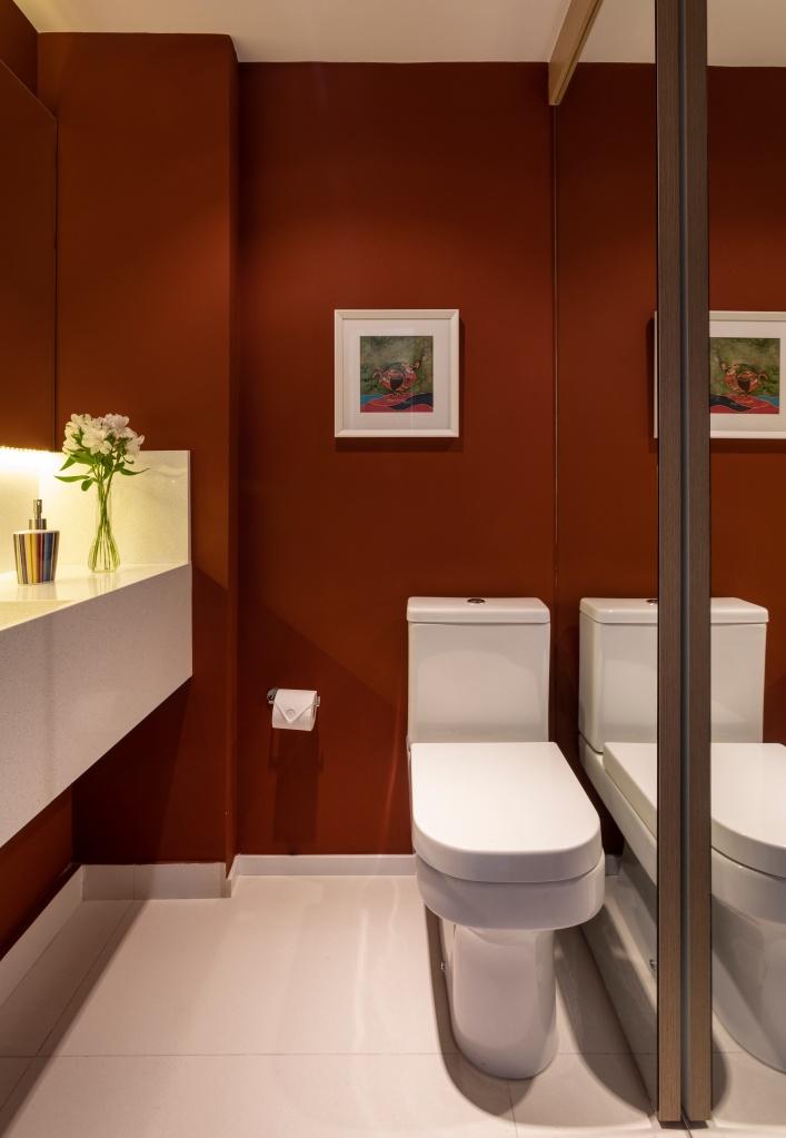 lavabo com armário porta de correr com espelho e paredes na cor terracota