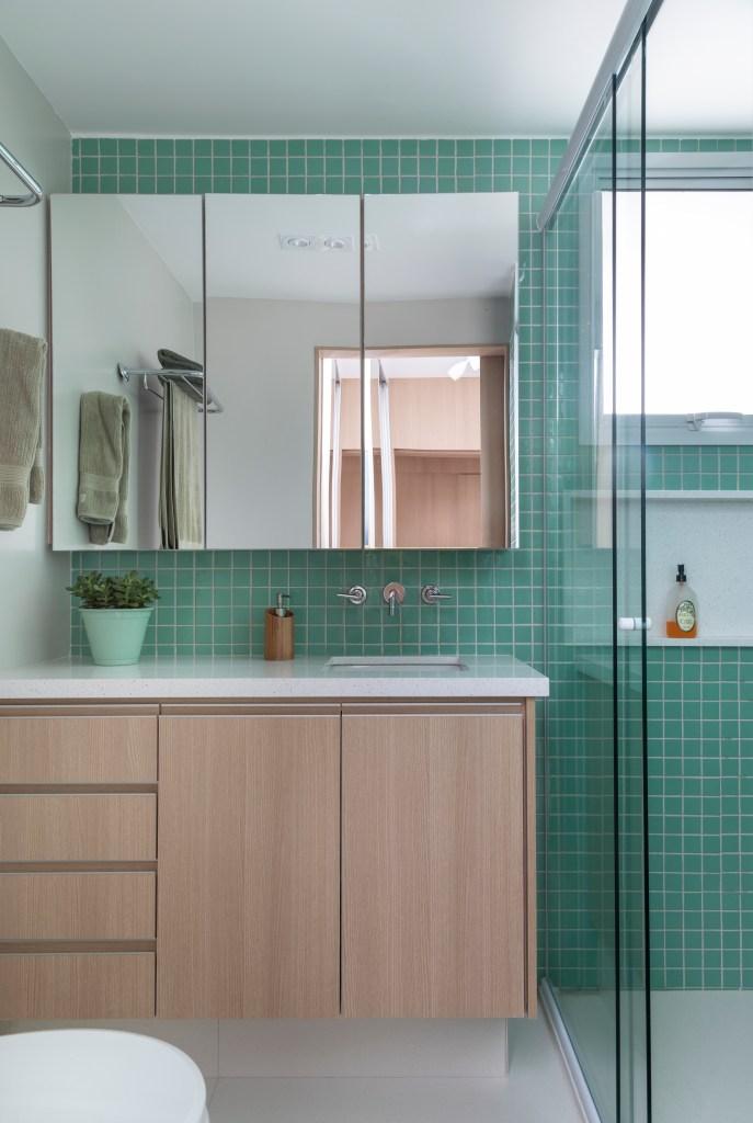 Banheiro com móvel de madeira clara e bancada em pedra branca. Na parede, ladrilhos verde claro e um móvel com espelho