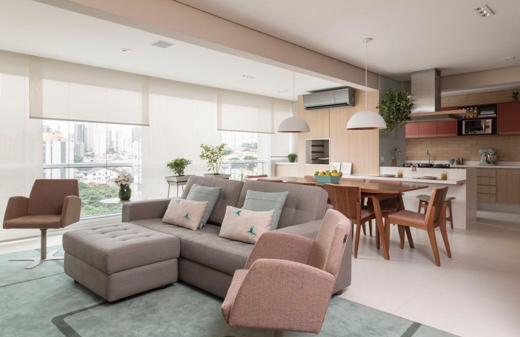 O sofá cinza é adornado com duas almofadas verde claro e duas brancas. No chão, um tapete verde. Uma poltrona em tom rosa claro completa o ambiente. Ao fundo, a mesa de jantar de madeira com cadeira no mesmo material