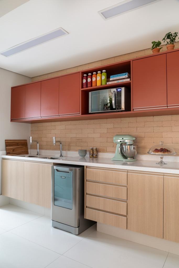Cozinha com armários térreo em madeira clara e bancada em pedra branca e armários aéreos na cor goiaba