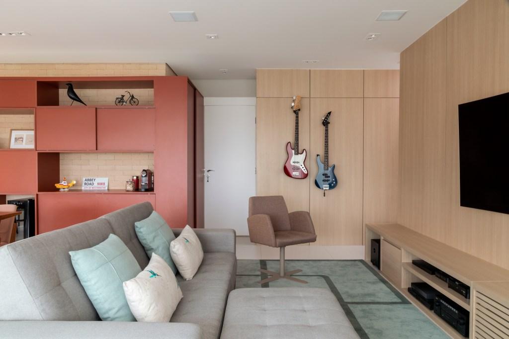 Sala de estar com marcenaria na parede, com duas guitarras presas a ela em suportes. O sofá cinza é adornado com duas almofadas verde claro e duas brancas. No chão, um tapete verde. Ao fundo, do lado esquerdo, armário na cor goiaba