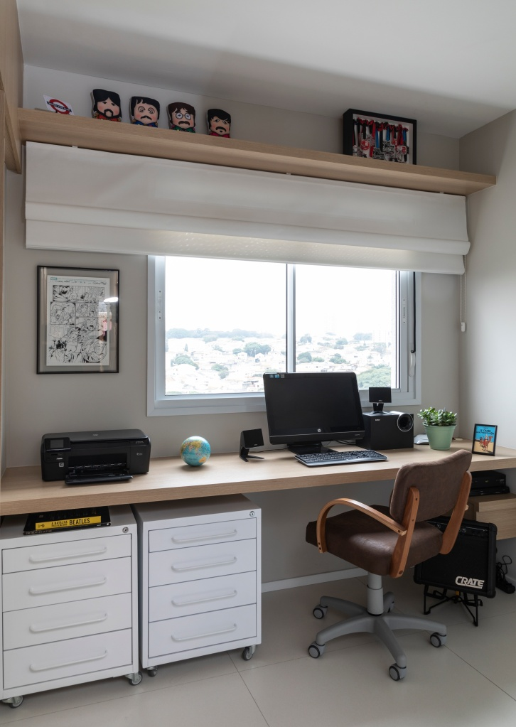 escritório constituído por bancada, cadeira ergonômica, móveis soltos e iluminação natural.