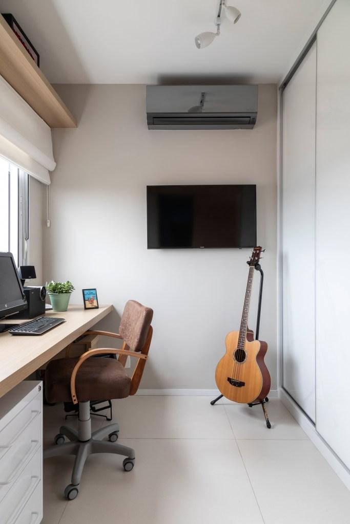 escritório constituído por bancada, cadeira ergonômica, móveis soltos e iluminação natural. No canto, uma Tv e um violão em pé no suporte