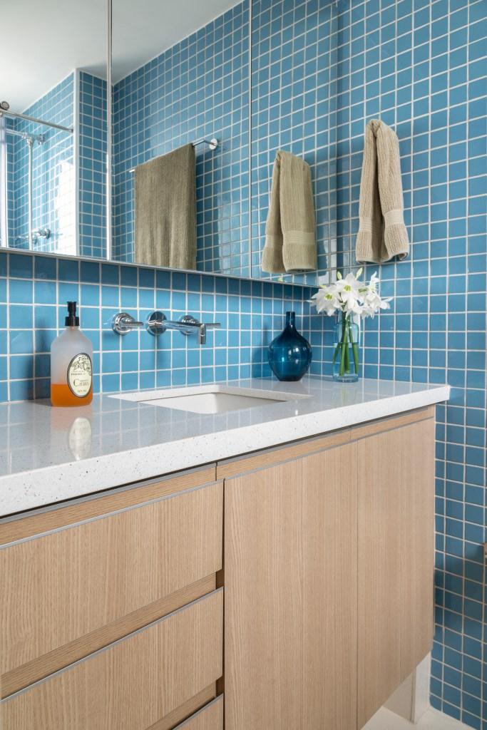 Banheiro com móvel de madeira clara e bancada em pedra branca. Na parede, ladrilhos azul claro e um móvel com espelho
