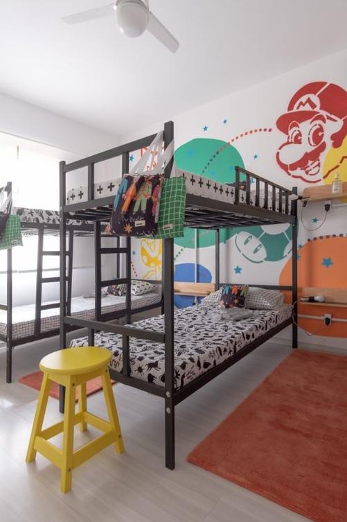 Beliche preta com camas com roupas de cama com grafismos brancos e pretos. Na parede, desenhos do game Mario