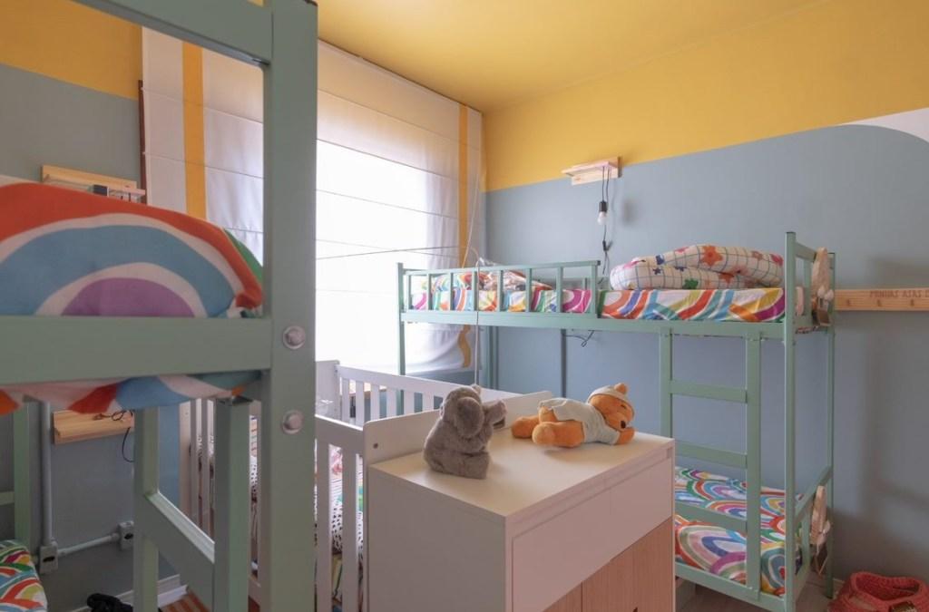 Duas beliches verde água com roupas de cama com grafismos de arco-íris. No centro do quarto, um berço branco e duas pelúcias. Paredes azuis e amarelas