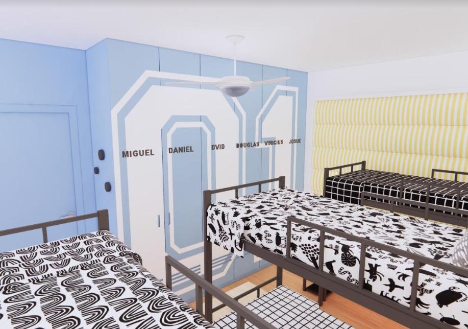 Três beliches pretas com roupas de cama com grafismos brancos e pretos. Armários azuis claros. Em cada porta está escrito o nome de uma criança