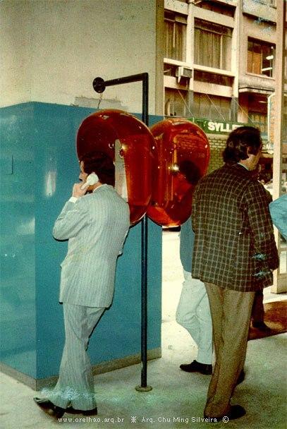 Homem de terno falando em orelhão laranja transparente encostado em parede azul. Foto de época