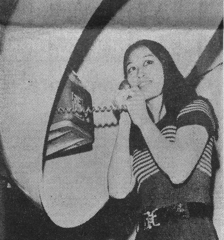 Chu Ming Silveira falando no orelhão posando para foto em jornal