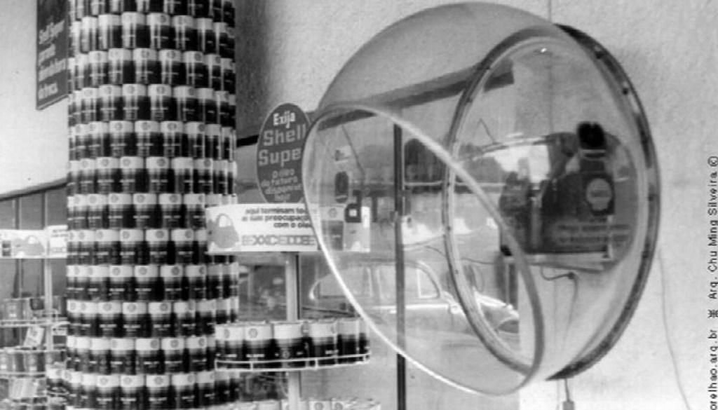Orelhão transparente dentro de mercearia. Latas empilhadas ao fundo