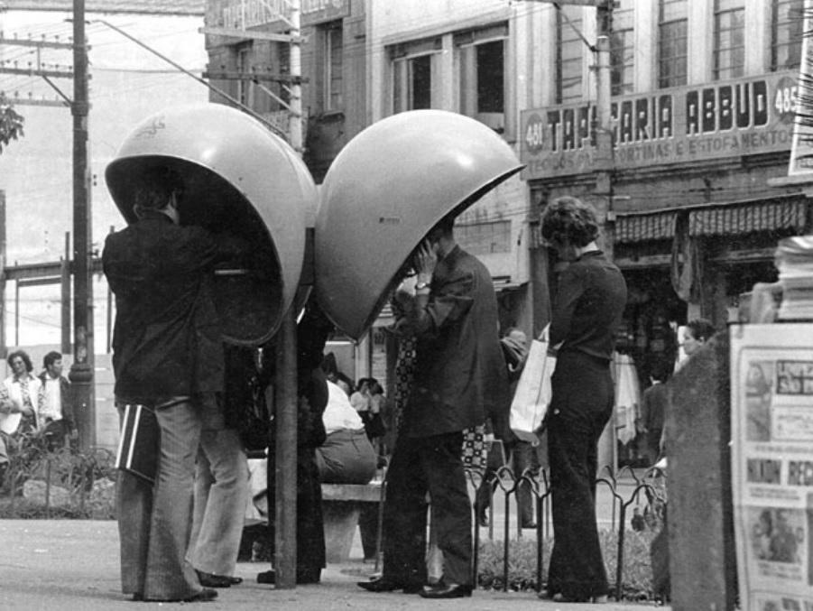 Conjunto de três orelhões em cidade com filas de pessoas para falar. Foto preta e branca