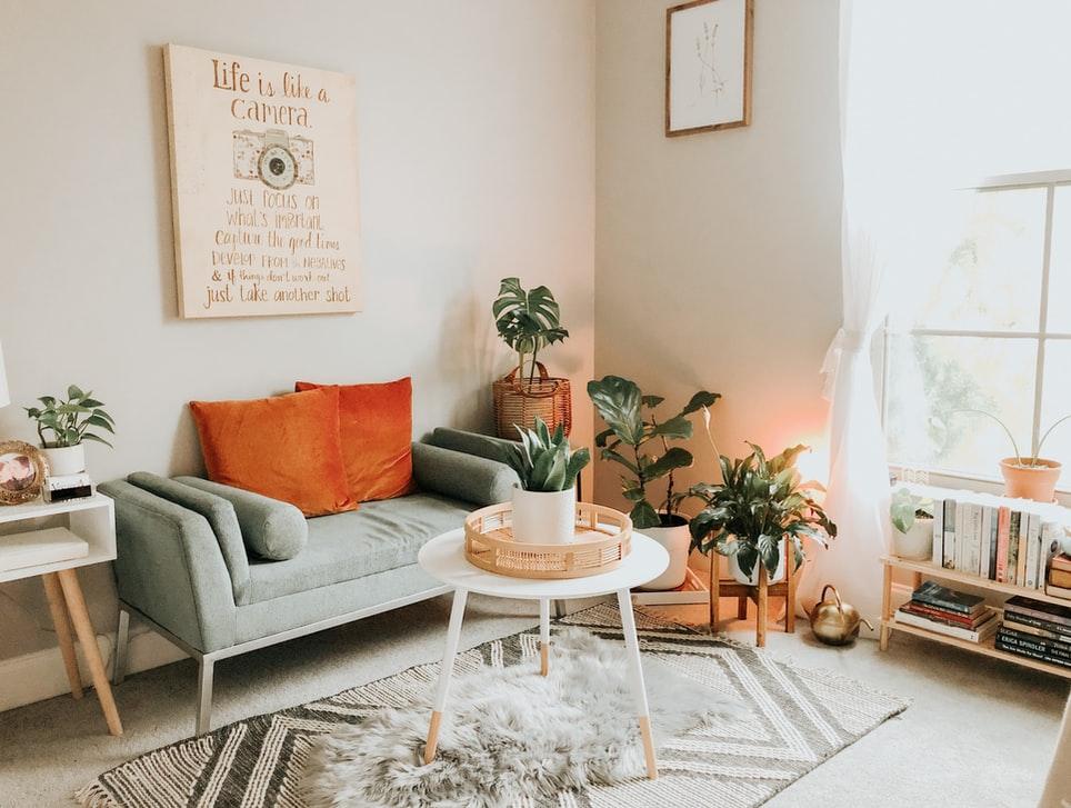 Sala de estar com um sofá cinza, emsa de centro branca, tapete e plantinhas ao lado do sofá