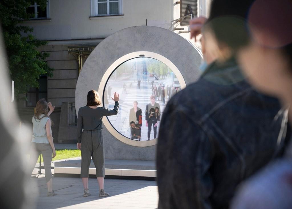 Círculo com tela no centro que permite ver outro lugar do planeta. Atrás, uma grande construção. À frente, diversas pessoas olham através do portal e acenam para o outro lado