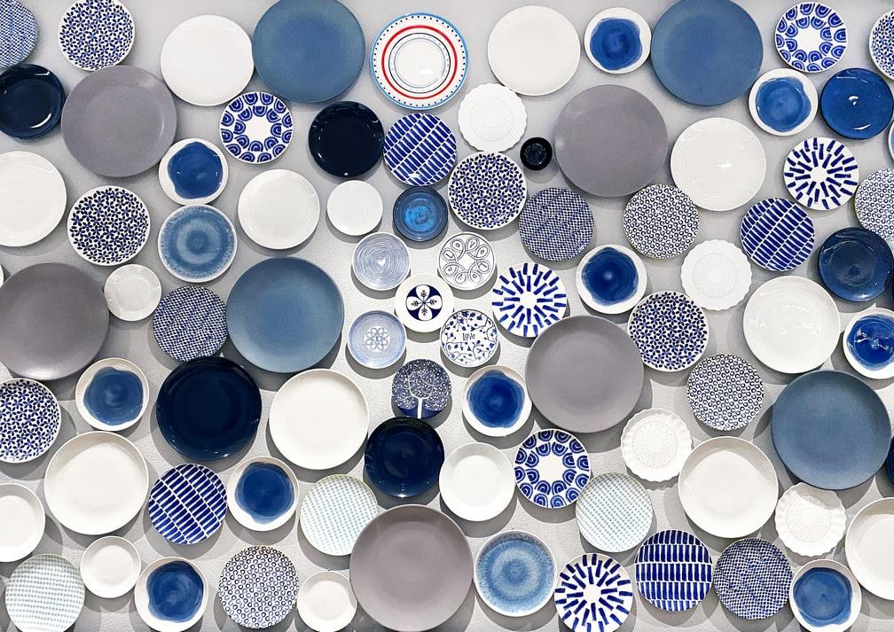 Composição com diversos pratos azuis e brancos em fundo branco