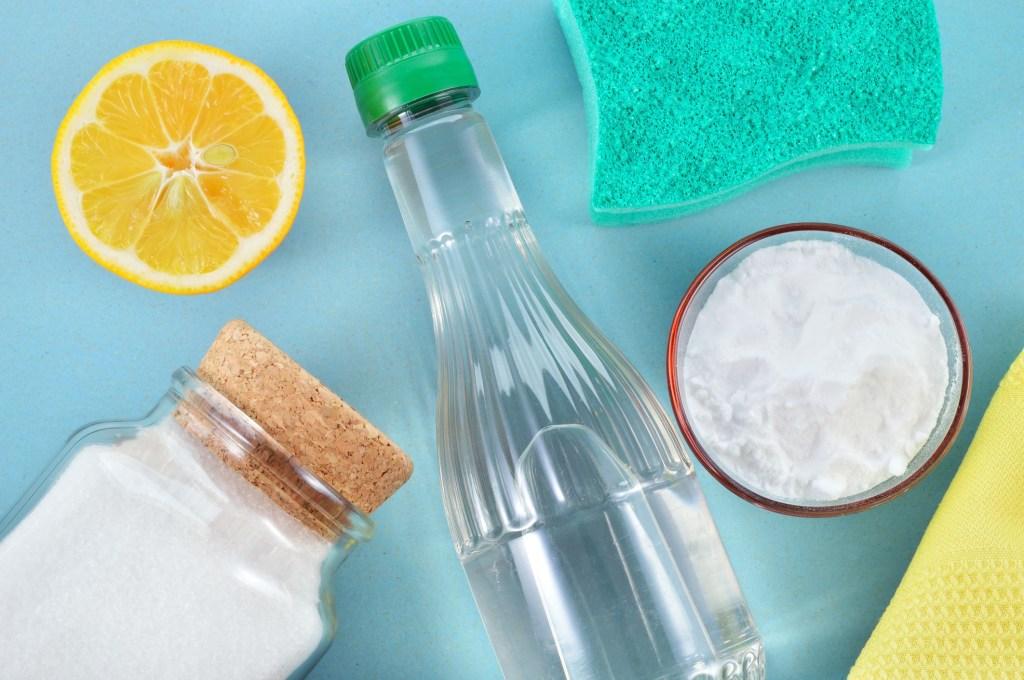 Fundo azul com garrafa co liquido transparente, bicarbonato de sódio, esponja e limão