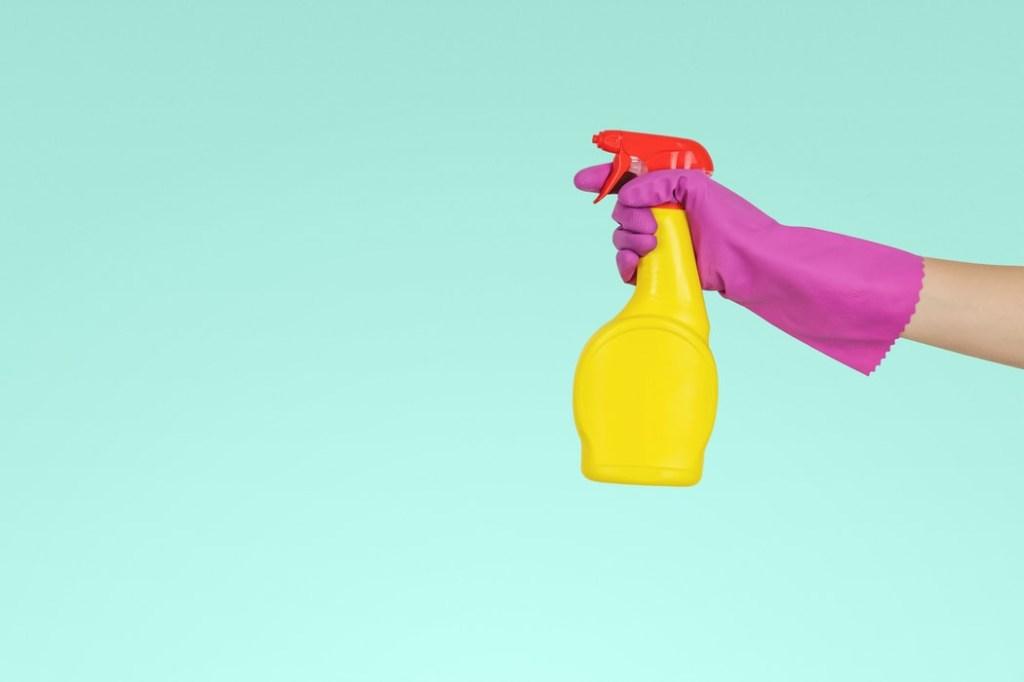 Fundo azul com um mão com luva rosa segurando uma embalagem de spray amarela