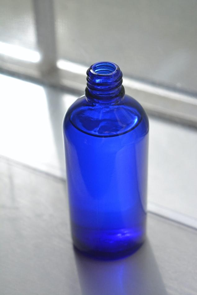 emabalagem azul com liquido dentro sobre bancada de pedra