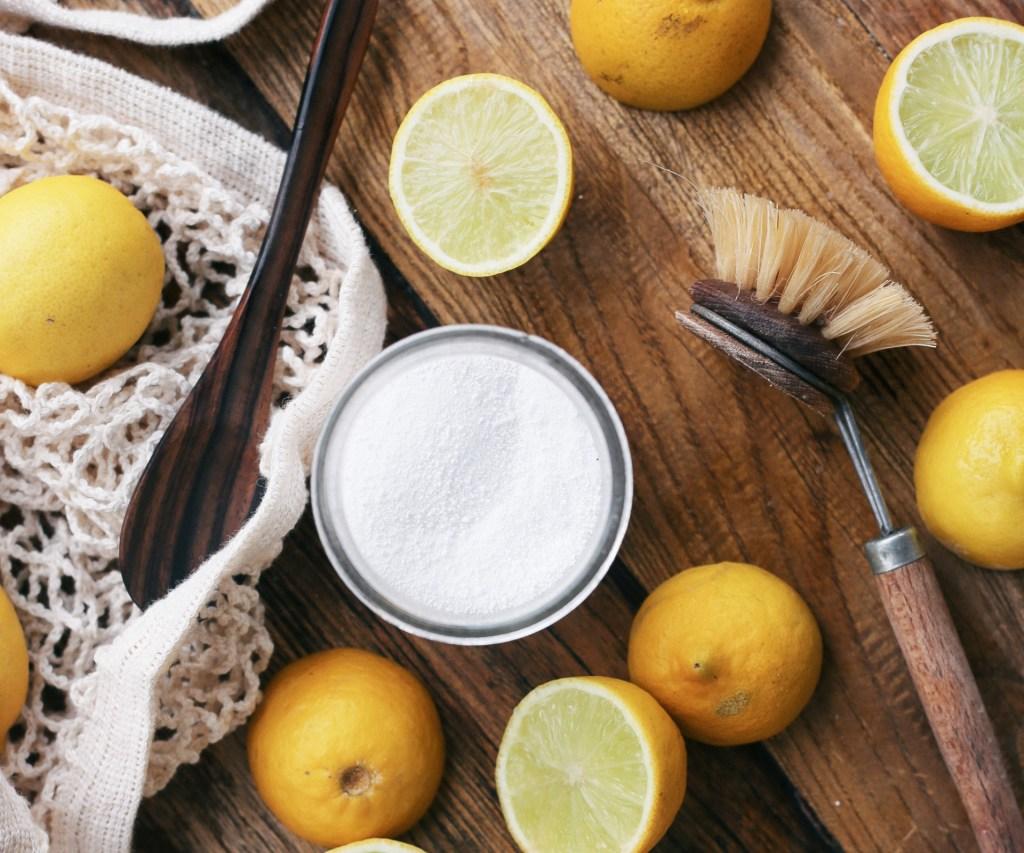 bicarbonato de sódio, limões e escove de madeira sobre bancada de madeira