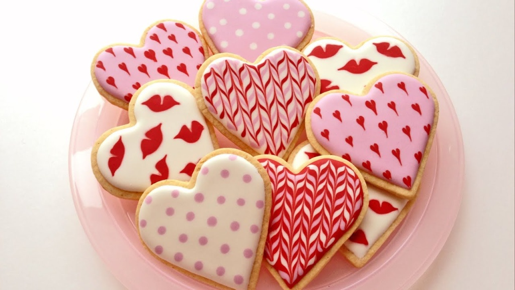 Biscoitos em forma de coração decorados com padrões rosa e vermelhos, corações menores, lábios