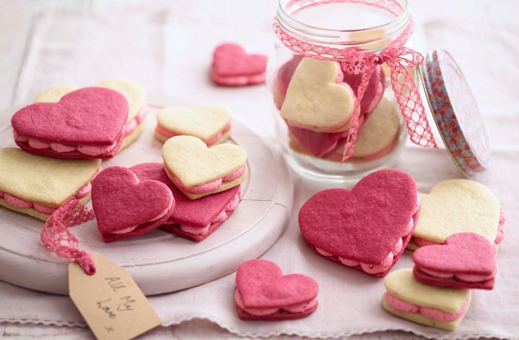 Biscoitos em formato de coração amarelos e rosas. Pote de vidro com fita rosa e mais biscoitos dentro ao fundo
