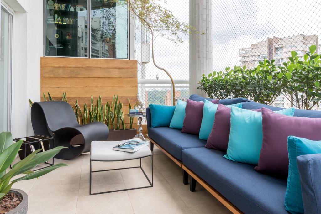 Varanda aberta com porcelanato, mesa de centro branca, com sofá azul com almofadas em azul claro e roxo. Ao lado, com plantas ao fundo, uma cadeira de design completa o ambiente