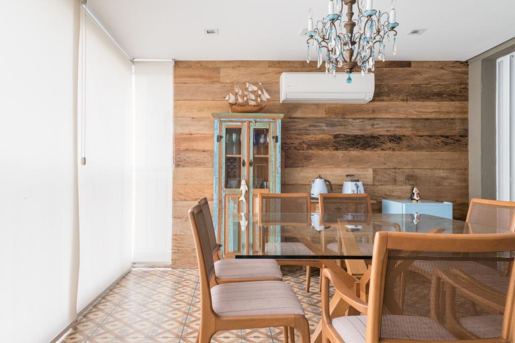 Sala de jantar com parede e piso da varanda fechada por vidro e resguardada pela persiana, madeira de demolição na parede e o piso que remete ao ladrilho hidráulico