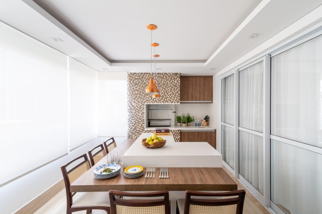 Na varanda gourmet deste apartamento, vê-se bancadas de quartzo e, em torno da churrasqueira, mosaico de pastilhas de cerâmica