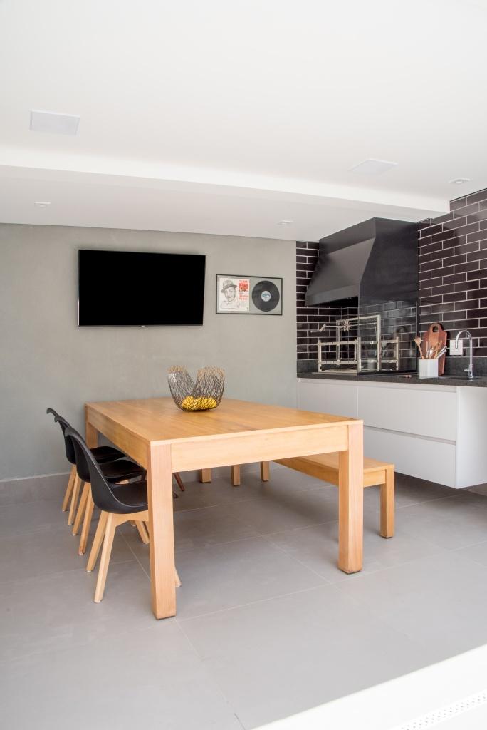 Área gourmet, com paredes cinzas e TV pendurada em uma delas, área da churrasqueria com revestimento de tijolinhos pretos, com bancada branca, mesa de madeira com um banco no mesmo material e três cadeiras com assentos pretos