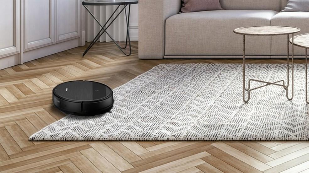 Sala com piso de taco e tapete preto e branco com aspirador entre os dois
