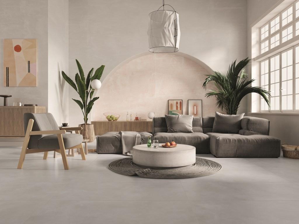 Sala de estar com piso de cimento queimado, com sofá e poltrona cinza