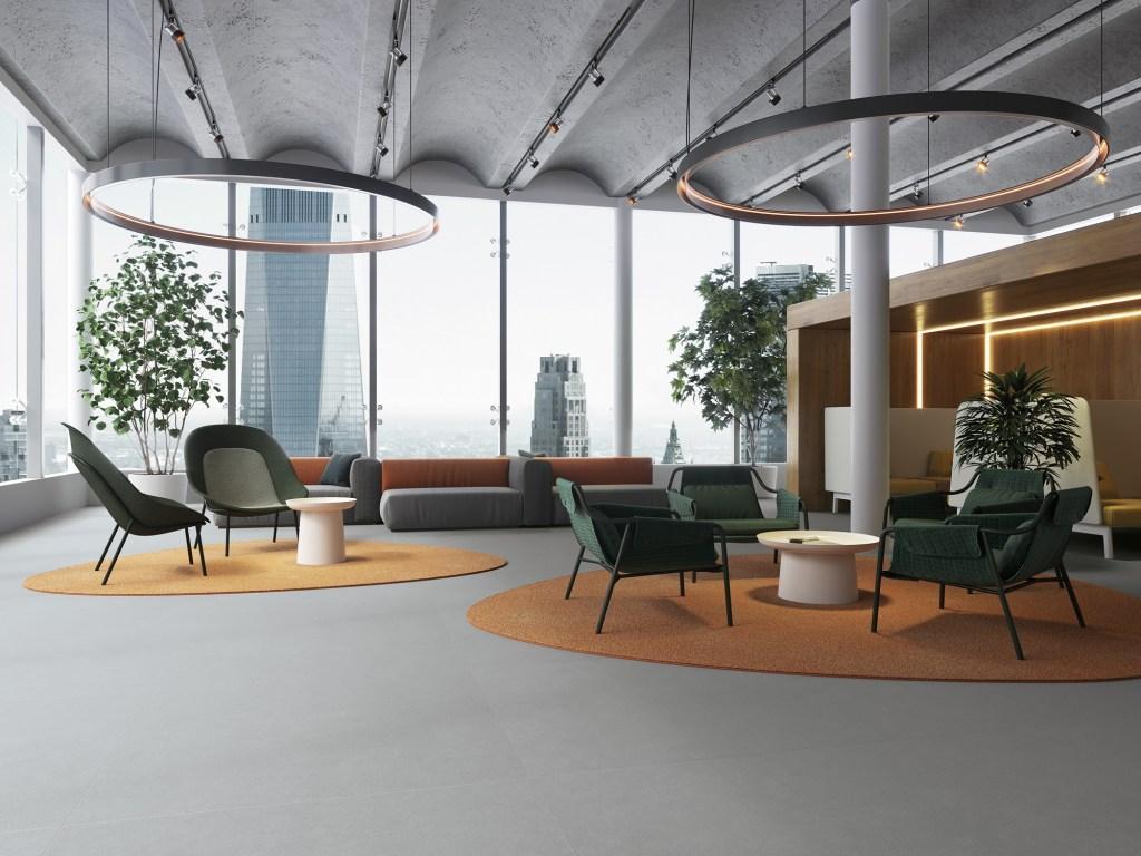 Espaço amplo, com cadeiras e mesas seccionados por tapetes laranja e amarelo