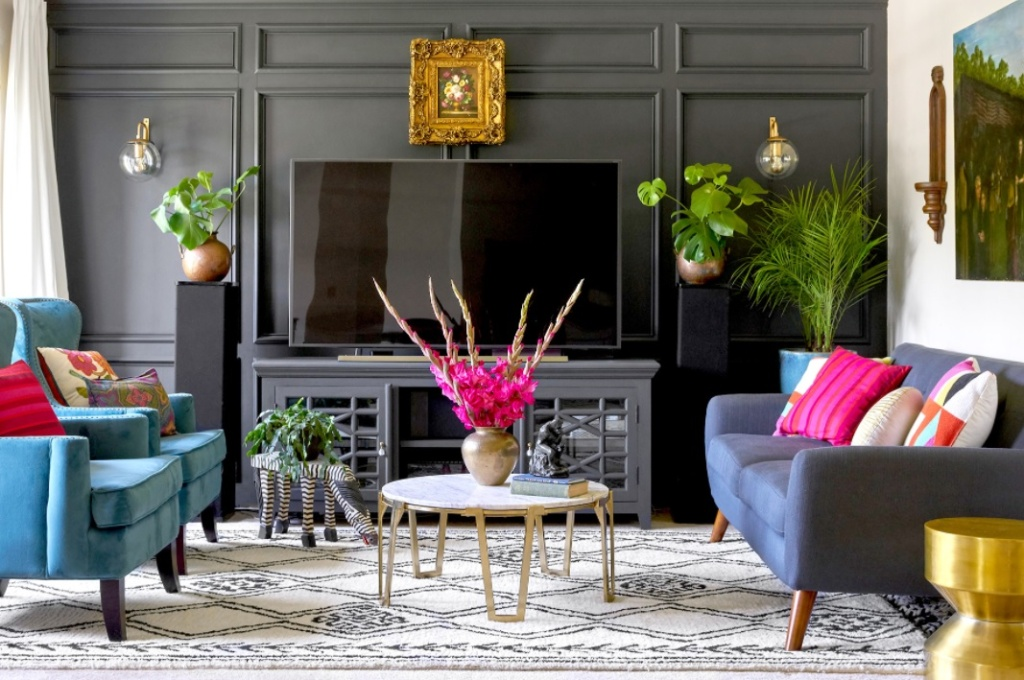Sala de TV com sofá e duas poltronas azuis. Parede preta. Mesa de centro com flores pink. Almofadas pink. Duas luminárias de parede, uma em cada lado da tv