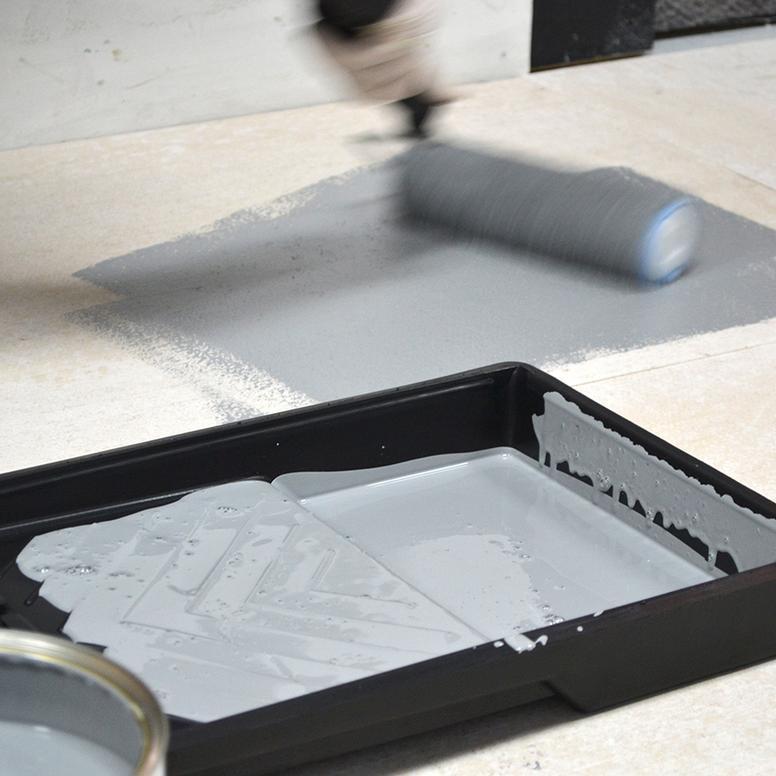 Chão sendo pintado de cinza com rolo grande, ao lado de bandeja com tinta cinza