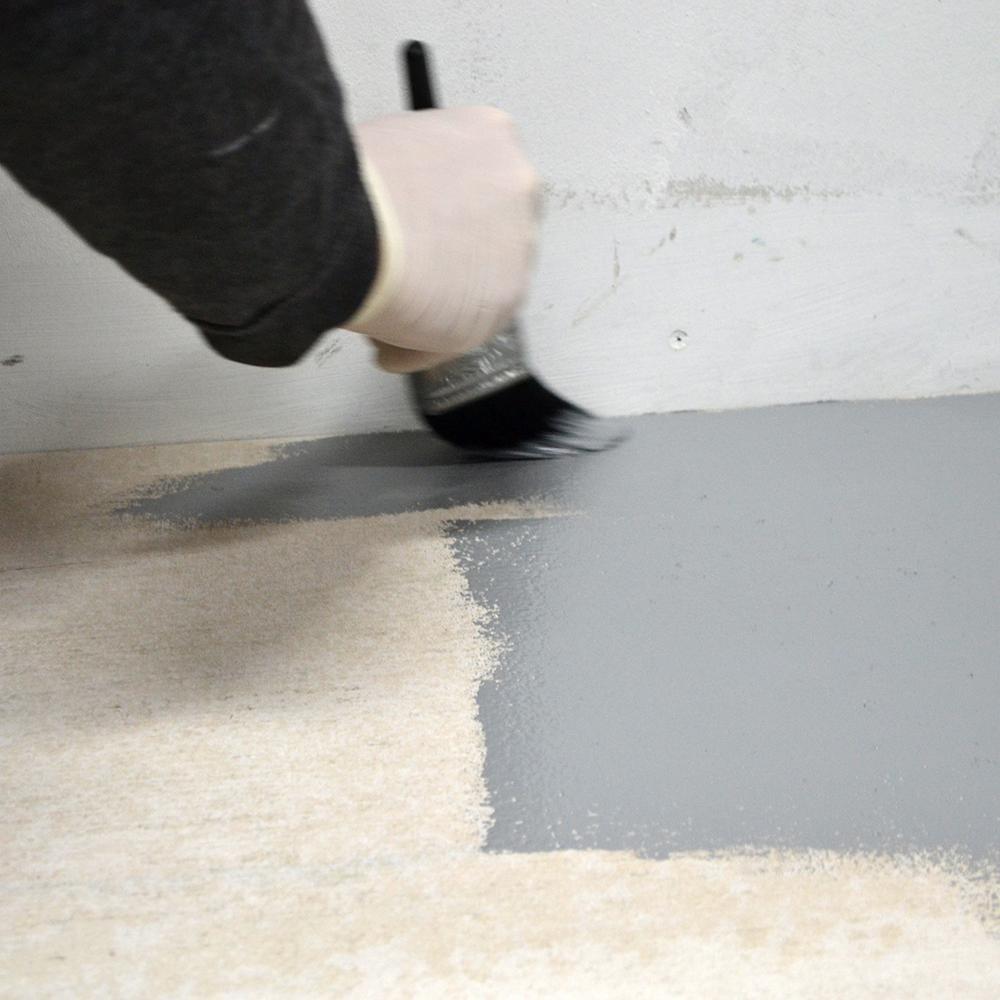 Chão sendo pintado de cinza com pincel