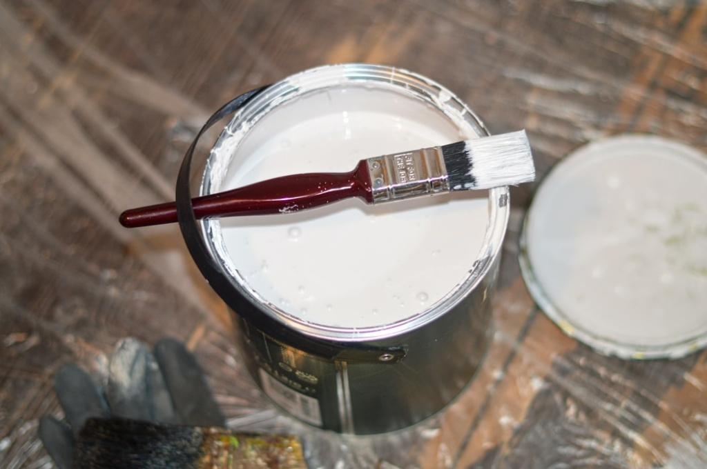 Lata de tinta branca aberta com pincel em cima sobre piso de madeira