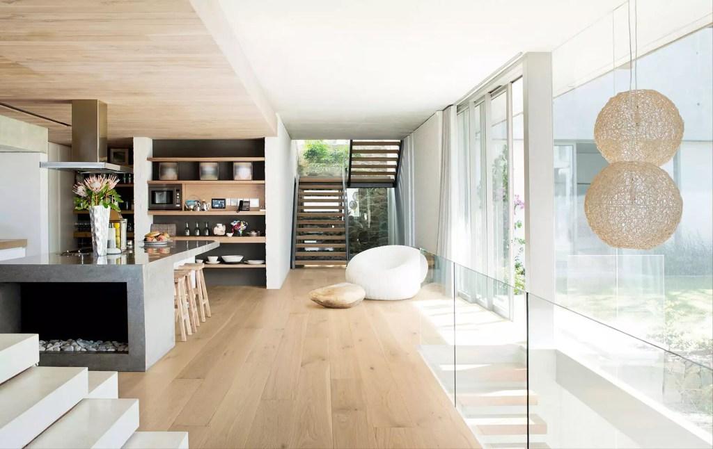 Casa com planta integrada, com parede de vidro e madeira clara no chão e no teto