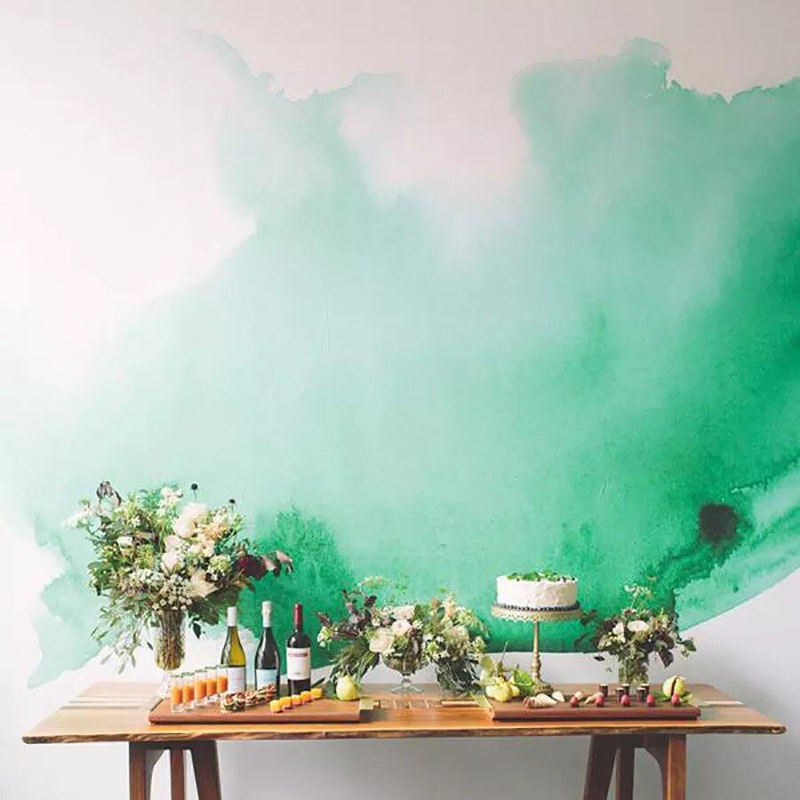 Parede branca com tinta verde aquarelada. À frente, um aparador de madeira, com vasos de flores