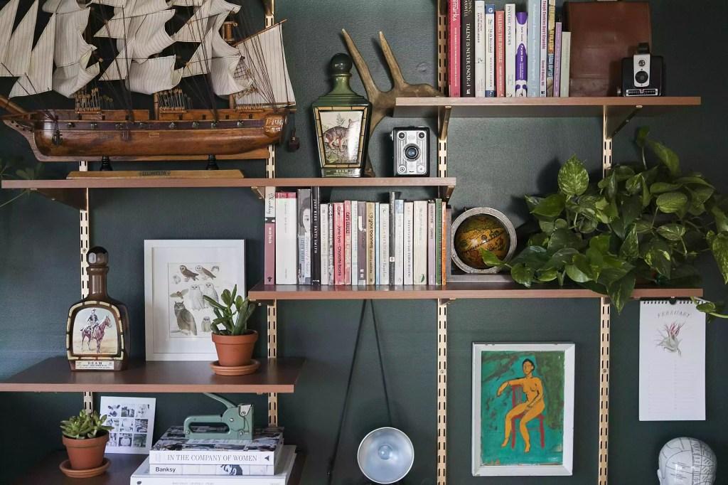 Estante de madeira, com prateleiras presas por cordas em alturas irregulares, com fundo vazado para a parede verde esmeralda. Livros, quadros e itens decorativos estão na estante