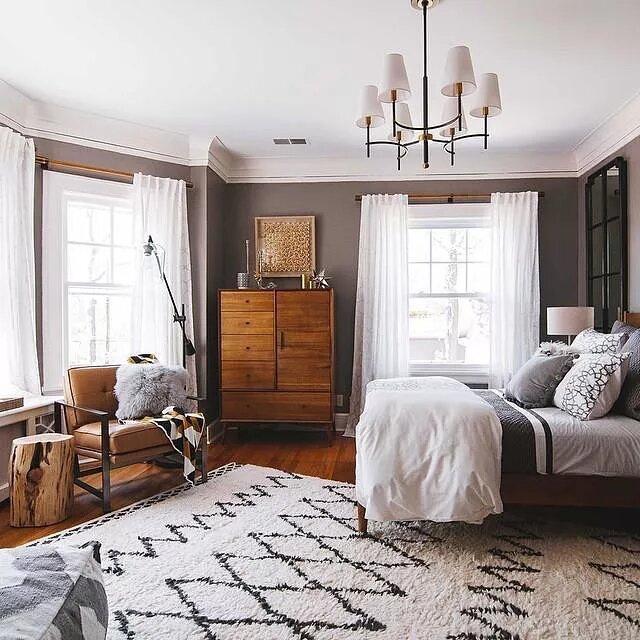 Quarto com paredes cinzas e móveis de madeira escura. No chão um tapete branco com padrão geométrico. A cama está do lado direto, com muitos travesseiros, sobre um lustre