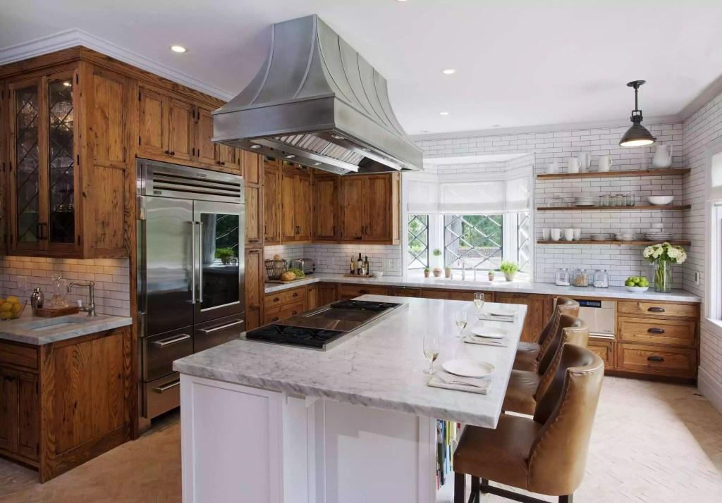 Cozinha com bancada branca no centro, com armários de madeira nas paredes