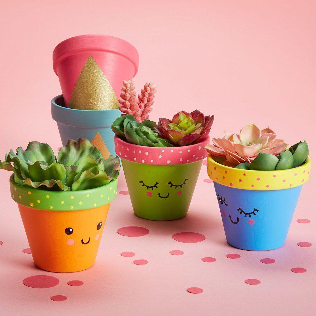 Vasos de planta coloridos com rosto desenhados na frente