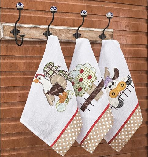 Três panos de copa pendurados com estampas de patchwork. Um com galinha, um com árvore e um com vaquinha.
